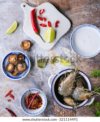 Ingredients for spicy Thai soup Tom Yam coconut milk, chili peppers, shiitake mushrooms and shrimps in ceramic bowls over stone background. Top view.  - stock photo