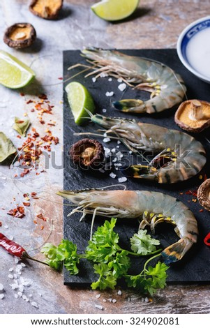 Ingredients for spicy Thai soup Tom Yam coconut milk, chili peppers, shiitake mushrooms and shrimps over black slate board on stone background. - stock photo