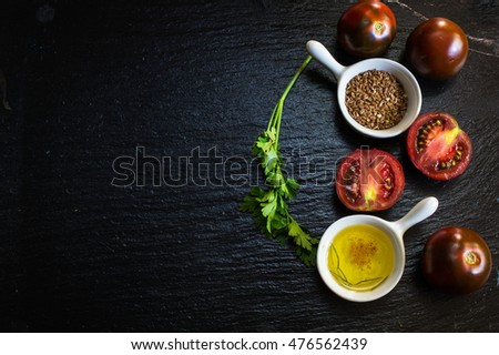 Ingredients for summer salad - tomatoes, parsley, flax seeds and oil.