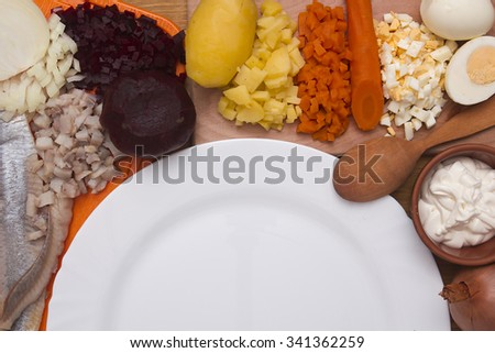 Ingredients for the herring salad with an empty plate. - stock photo