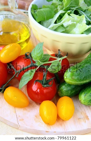 ingredients for the salad, cucumbers, tomatoes, olive oil and green salad mix - stock photo