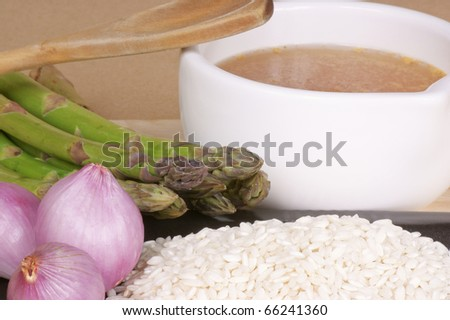 "Ingredients for the typical italian dish ""risotto con gli asparagi"": rice, asparagus, shallot and vegetable stock. - stock photo"