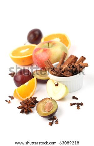 Ingredients for winter hot drink. Apples, oranges and plums with cinnamon, anise and clove on white background - stock photo