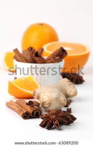 Ingredients for winter hot drink. Orange with cinnamon, ginger, anise and clove on white background - stock photo