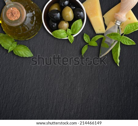 Ingredients of italian cuisine  - basil, parmesan, olives  and olive oil - on dark background - stock photo