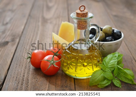 Ingredients of italian cuisine  - cherry tomato, basil, parmesan and olive oil - on wooden background - stock photo