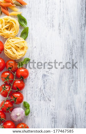 ingredients pasta tomatoes basil frame on white wooden background  - stock photo