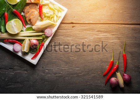 Ingredients set for Thai spicy soup (Tom-yum) include lemon, galangal, red chili, red onion, lemongrass, and kaffir lime leaf on wood table in low key morning scene with blank area for text or message - stock photo