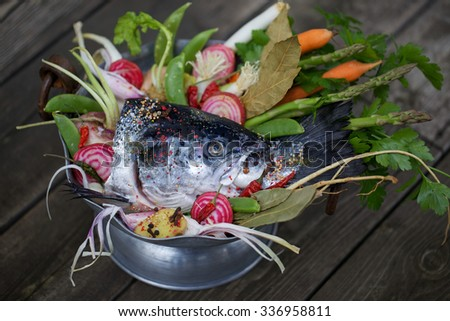Ingredients to fragrant broth: fresh head of norwegian salmon, asparagus, carrots, garden vegetables, spices and herbs - stock photo