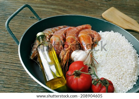 ingredients to prepare a spanish paella or arroz negro on a rustic wooden table - stock photo