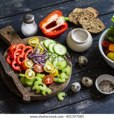 Ingredients to prepare vegetable salad - tomatoes, cucumber, celery, bell pepper, red onion, quail eggs, garden herbs and spices on a rustic wooden board. Healthy food - stock photo