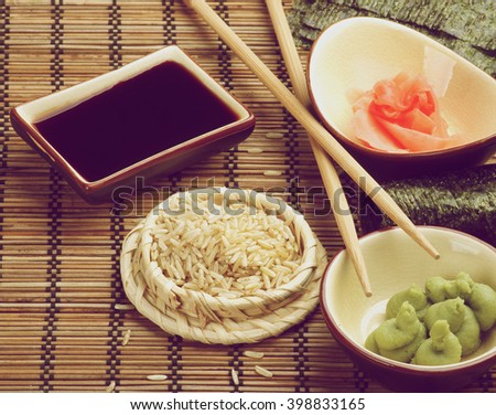 Ingredients to Preparing Sushi with Nori, Ginger, Wasabi, Rice, Soy Sauce and Two Chopsticks on Bamboo Straw Mat. Retro Styled - stock photo