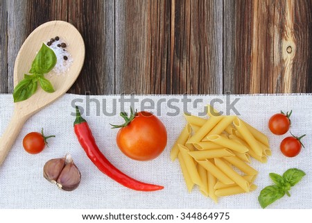 Ingredients (tomatoes, macaroni, a basil, garlic, pepper, salt) for cooking of penne with tomato sauce on old wooden background - stock photo