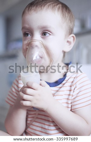 inhalation by nebulizer. a child in a mask by a nebulizer for inhalation during asthmatic attack. medical therapy if difficulty breathing, asthma, respiratory diseases - stock photo