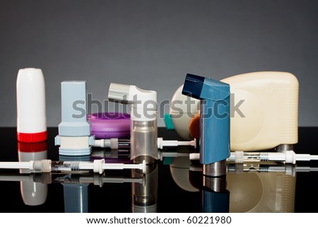 inhalers and syringes on a dark background - stock photo