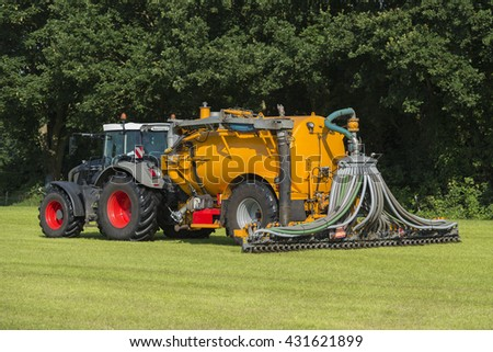 injecting manure in a pasture with a green tractor and yellow vulture tank car - stock photo