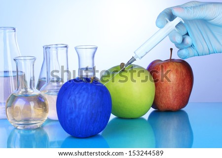 Injection into apple on blue background - stock photo