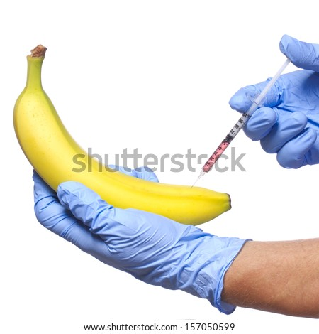 Injection into banana isolated on white background. Genetically modified fruit and syringe in his hands with blue gloves - stock photo