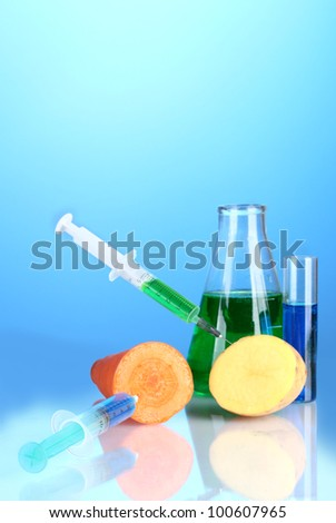 Injection into fresh vegetables on blue background - stock photo