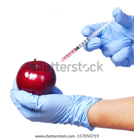 Injection into red apple isolated on white background. Genetically modified fruit and syringe in his hands with blue gloves - stock photo