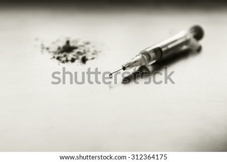 Injection syringe, and in the background a pile of white flour. Images of drug needles and drug. The picture is staged and there is no real drugs. Image includes a Tinted black effect. - stock photo