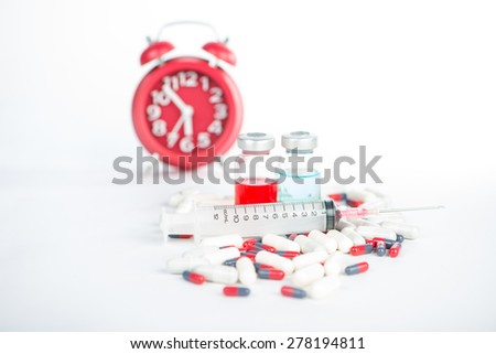 Injection syringe and medicine on red clock background - stock photo