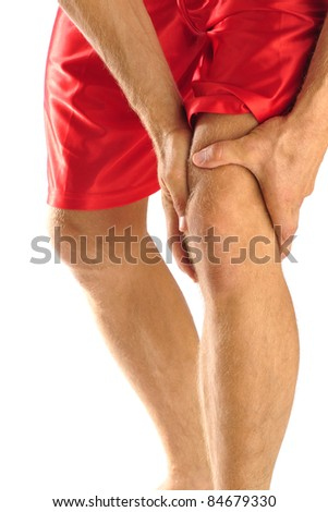 Injured athlete in pain clutches his knee - stock photo
