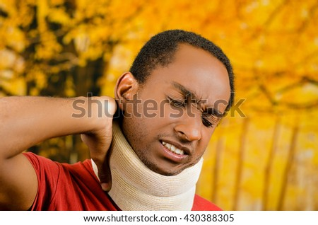 Injured black hispanic male wearing neck brace, holding hands in pain around support making faces of agony, yellow abstract background