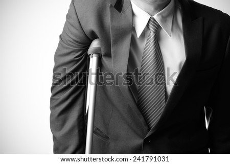 injured businessman in with crutches isolated on white background, insurance concept
