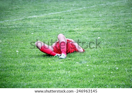Injured Football or Soccer Player Lying On The Ground - stock photo