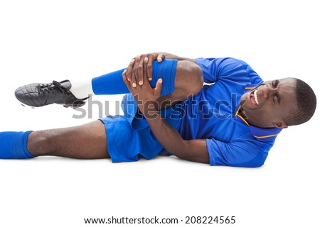 Injured football player lying on the ground on white background - stock photo