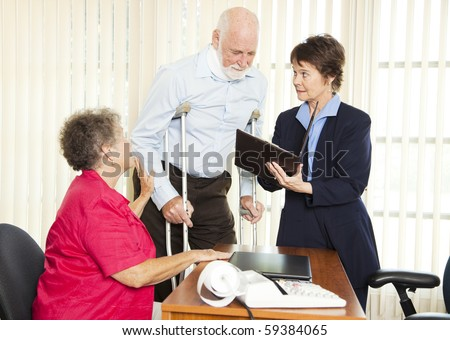 Injured man and his wife meet with a personal injury lawyer. - stock photo