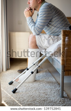 Injured Man in deep thoughts with a leg plaster - stock photo