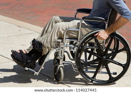 Injured man with a broken foot pushes himself along in his wheelchair. - stock photo