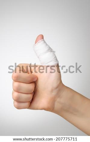Injured painful thumb with white bandage - stock photo