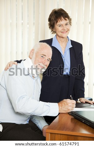 Injured senior man signing paperwork in his attorney's office. - stock photo