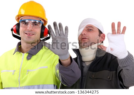 Injured tradesman comparing his hand to a healthy colleague - stock photo