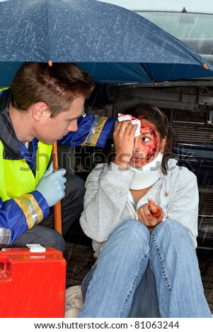 Injured woman being cared for in the rain - stock photo