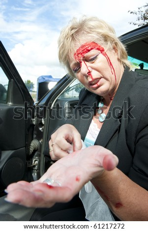 Injured woman checking her wounds after a car crash - stock photo