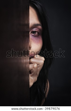 Injured woman hiding in dark, concept for domestic violence - stock photo