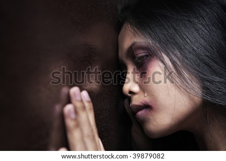 Injured woman leaning sadly on wooden wall, concept for domestic violence - stock photo