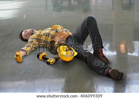Injured worker laying on floor inside building - stock photo