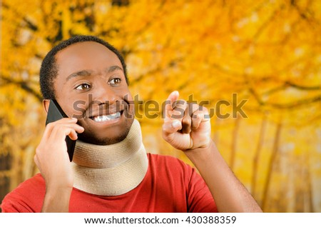 Injured young positive black hispanic male wearing neck brace and talking on phone smiling, yellow abstract background - stock photo