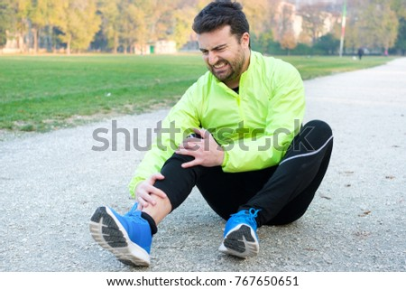 Injury running concept . Man having knee pain while training because overtraining