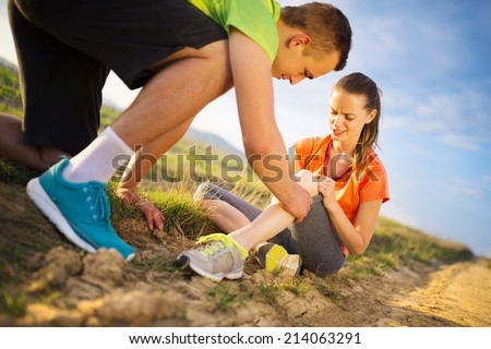Injury - sports woman with injured knee getting help from man touching her knee. - stock photo