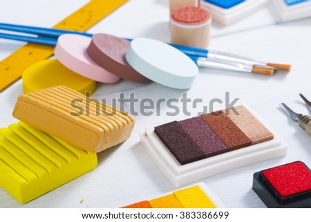 ink pads, brushes and carving cutters on white wood table
