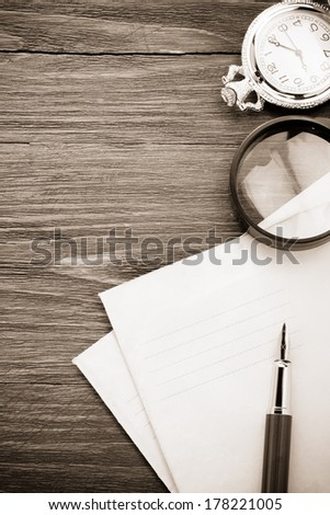 ink pen and old postal envelope on wood background - stock photo
