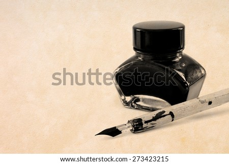 ink pot and ancient pen - with free text space - stock photo