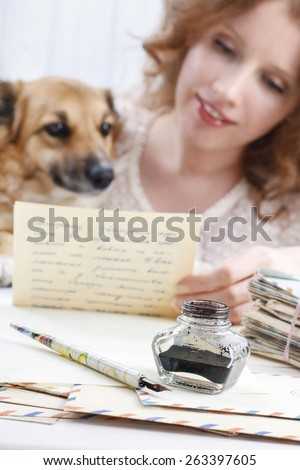 Ink stand. vintage pen and letters. Woman reading letter to a lovely puppy.  - stock photo