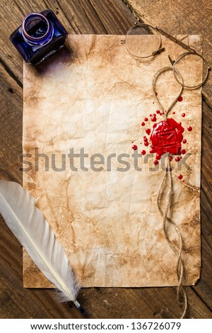 Inkstand, feather and red sealing wax on the vintage paper - stock photo